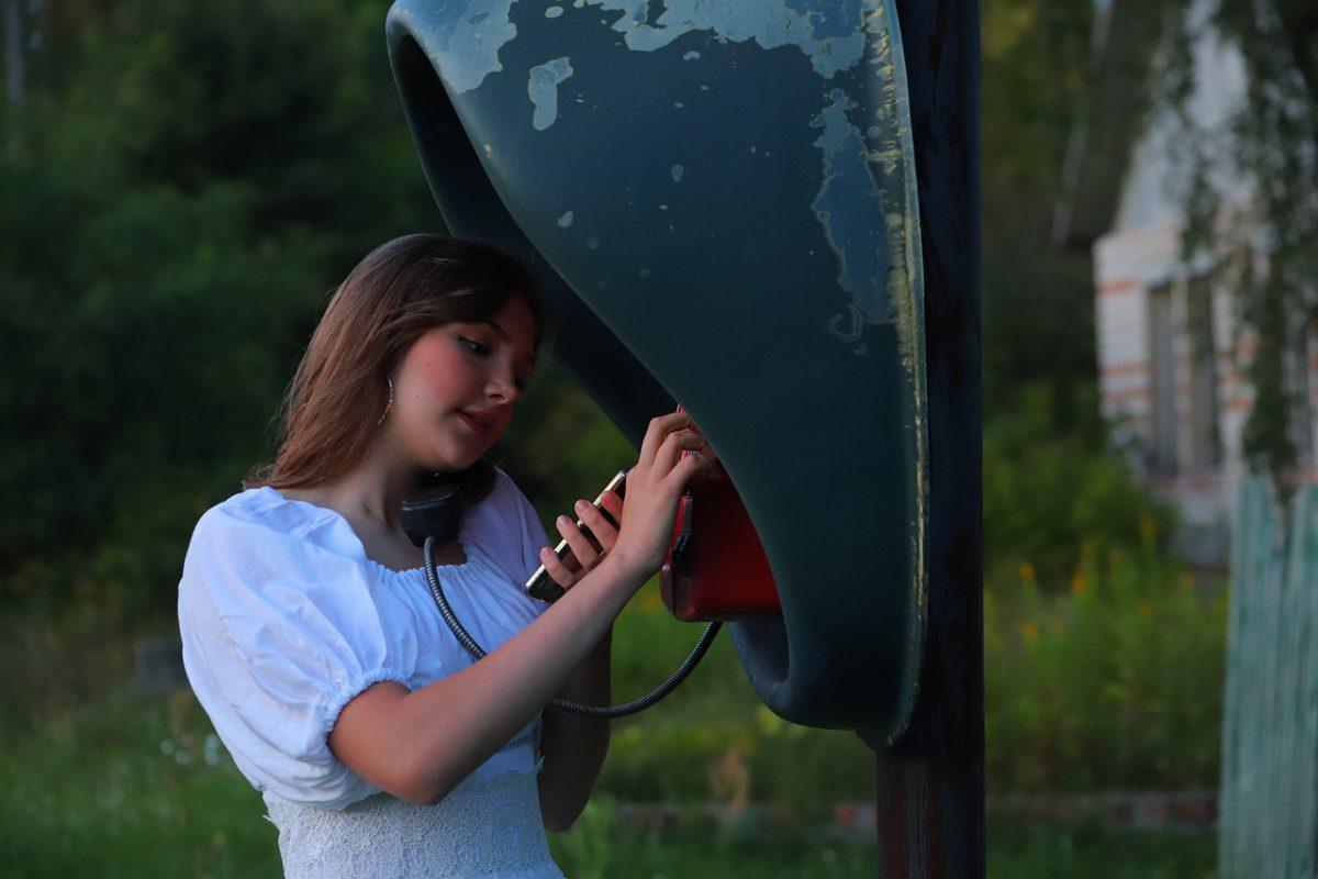 A woman using landline phone to make international calls.