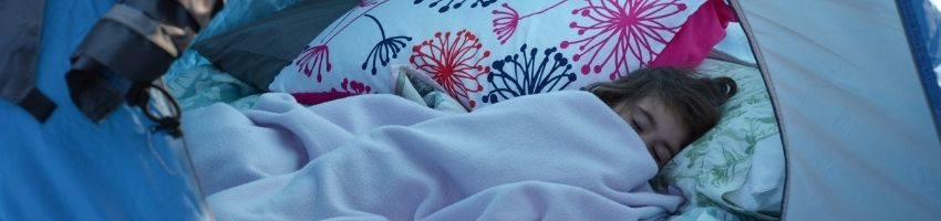 A child sleeping in a cozy air mattress.